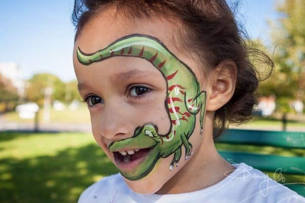 Young girl with face painting of dinosaur. © Danny Callcut.