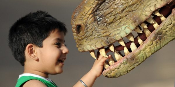 An Indian child plays with a park staff member wearing a dinosaur costume at the Adlabs Imagica theme park at Sangewadi some 100 kms south east of Mumbai on April 20, 2013. India's most elaborate theme park opened this week with special effect Hindu gods and Bollywood themed rides, aiming to tap a thirst for family entertainment among the country's rising middle class.  Adlabs Imagica, which cost about USD 294 million to create, opened its doors to the public on Thursday between the western cities of Mumbai and Pune, with capacity for 10,000 to 15,000 visitors a day. AFP PHOTO/ INDRANIL MUKHERJEE        (Photo credit should read INDRANIL MUKHERJEE/AFP/Getty Images)